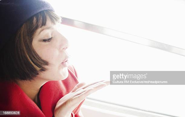 Woman blowing kiss on train