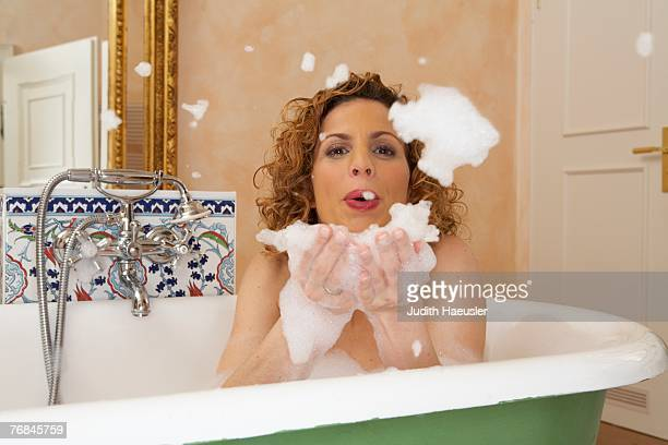 woman blowing lather from hands in bath, portrait