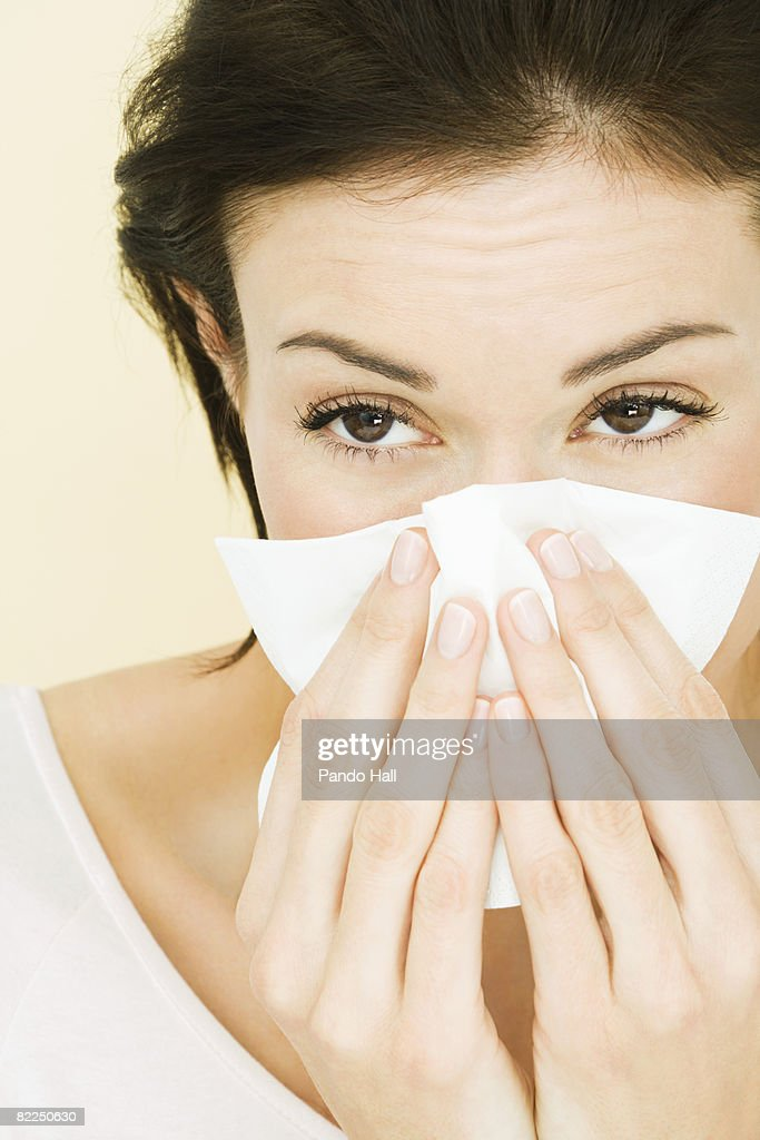 Woman blowing nose, close-up  : Stock Photo