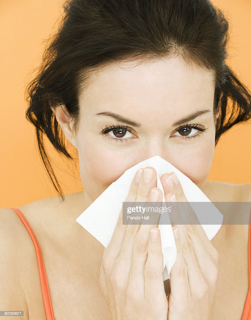 Woman blowing nose, close-up, portrait : Stock Photo