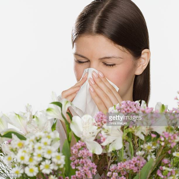 Woman blowing nose next to flowers