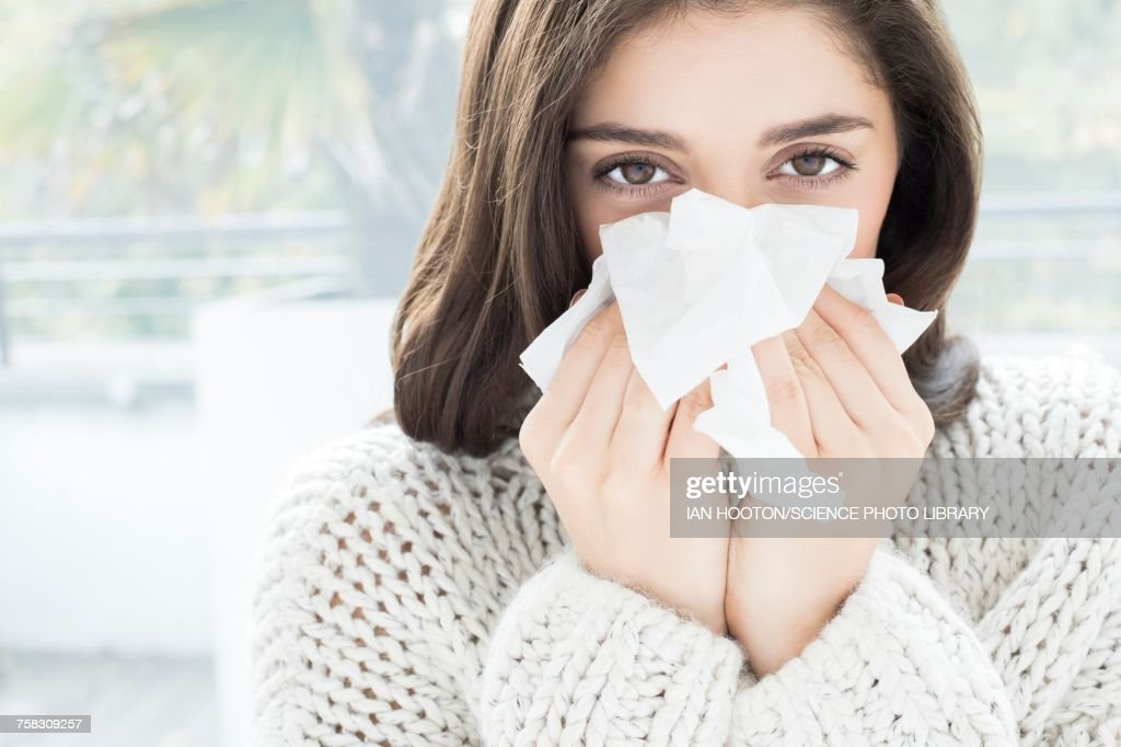 Woman blowing nose on tissue : Stock Photo