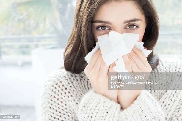 woman blowing nose on tissue - pneumonia stock pictures, royalty-free photos & images