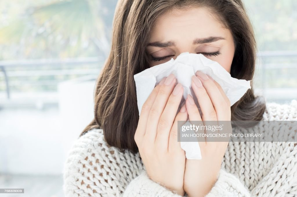 Woman blowing nose on tissue : Foto de stock
