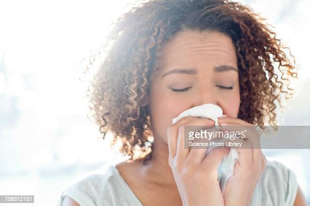 woman blowing nose on tissue - espirrando - fotografias e filmes do acervo