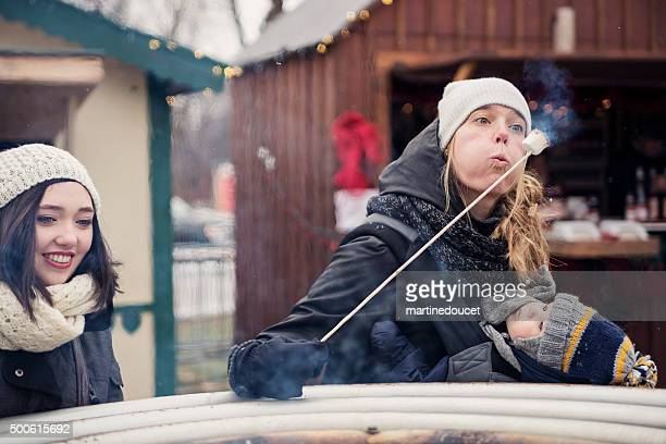 Woman blowing on burning marshmallow at winter market outdoors.