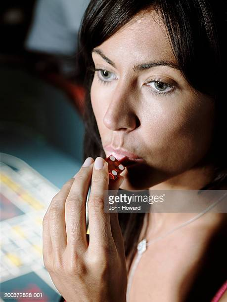 Woman blowing on dice, close-up