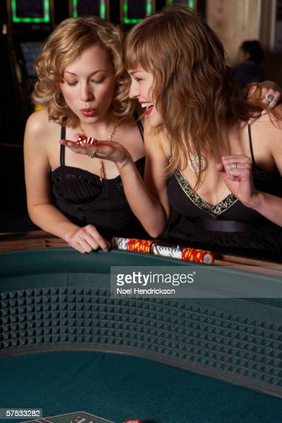 Woman blowing on dice for good luck in a casino