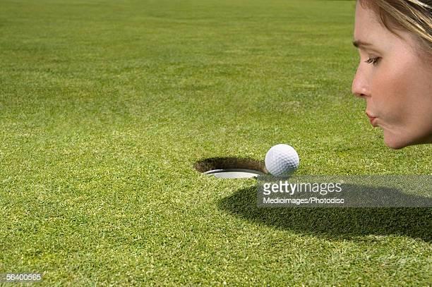 Woman blowing on golf ball near hole