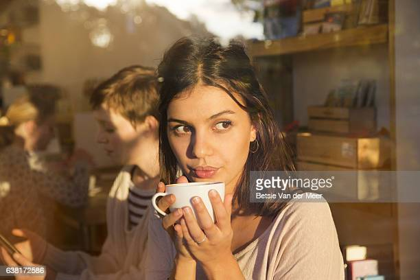 woman blowing on hot coffee while looking out of cafe window, sunlight reflections show in window. - brown eyes stock pictures, royalty-free photos & images