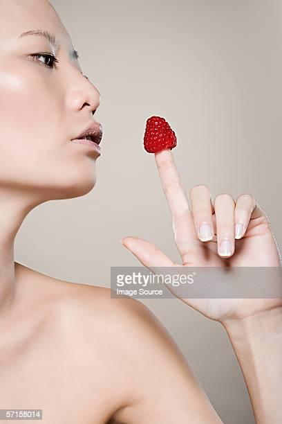 Woman blowing on raspberry