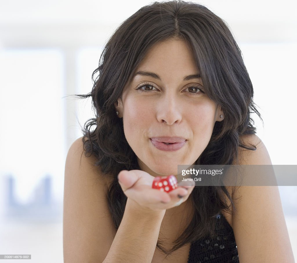 Woman blowing on red dice, close-up portrait. : Stock Photo