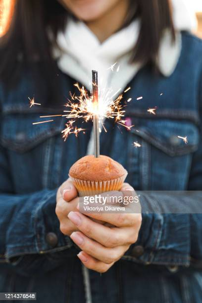 woman blowing out birthday candle on cupcake. happy birthday woman holding a cupcake - dessert topping stock pictures, royalty-free photos & images