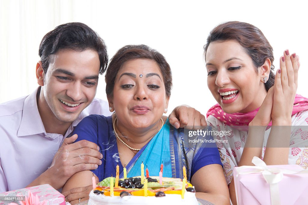 Woman blowing out candles on a birthday cake : Stock Photo