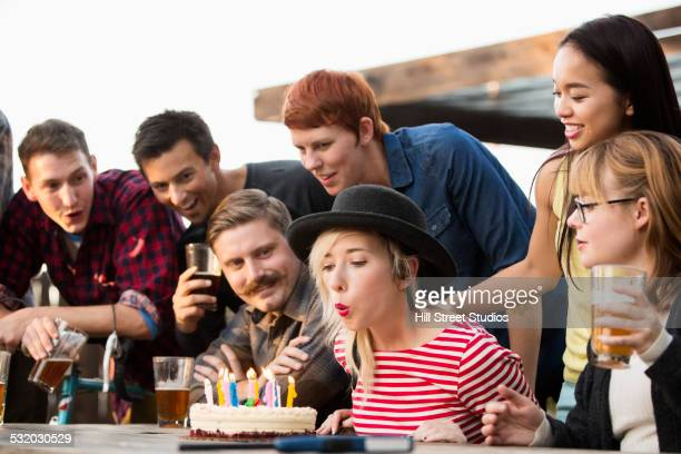Woman blowing out candles on birthday cake at party
