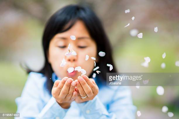 Woman blowing petals out of her hands