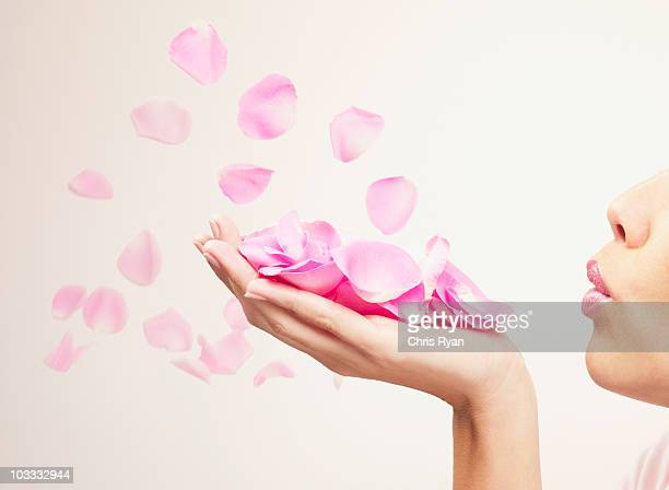 Woman blowing pink rose petals