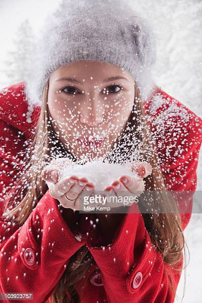 Woman blowing snow off her hands