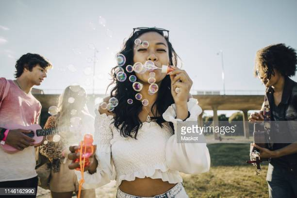 woman blowing soap bubbles while friends playing ukulele during music event - konzert stock-fotos und bilder