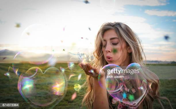 Femme soufflant étoiles confettis bulles dans domaine