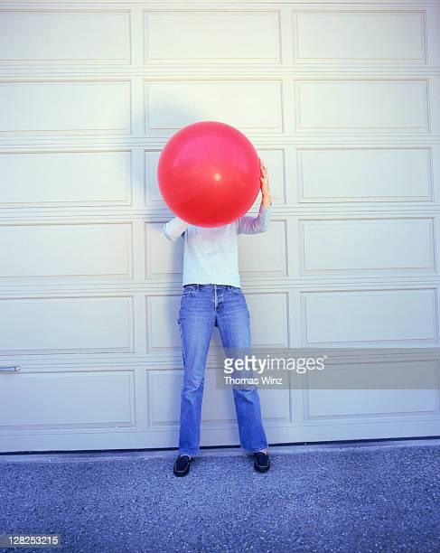 Woman blowing up balloon in front of garage door, USA