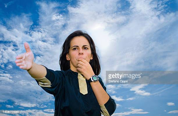 woman blowing whistle against blue sky - female umpire stockfoto's en -beelden
