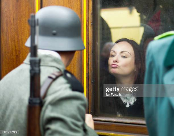 A woman blows a kiss to a reenactor wearing German Army uniform as he stands guard on the platform during the North Yorkshire Moors Railway 1940's...