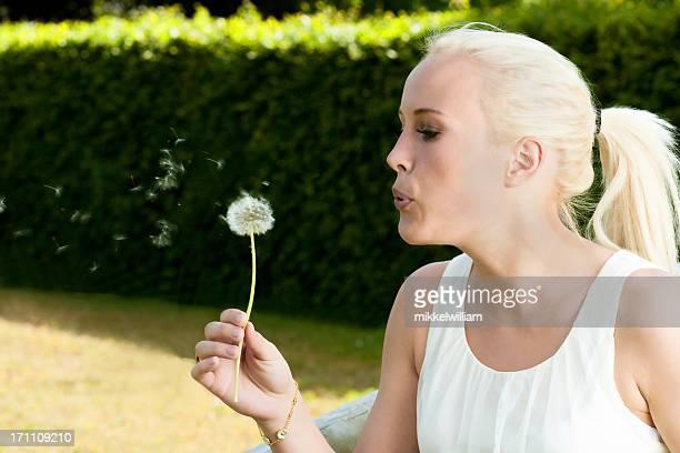 Woman blows air at a dandelion