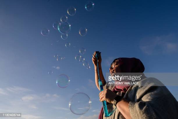 A woman blows bubbles as she attends a vigil in memory of the twin mosque massacre victims in Christchurch on March 24 2019 New Zealand will hold a...