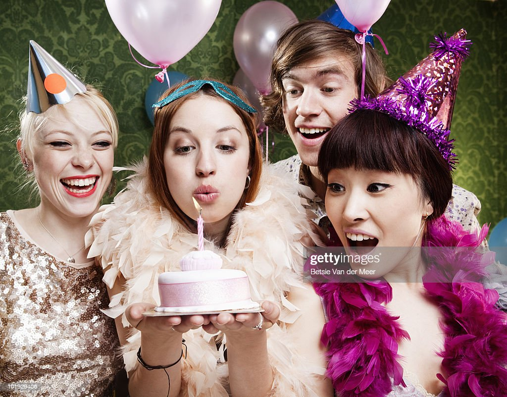 woman blows out candle on cake, with friends.  : Stock Photo