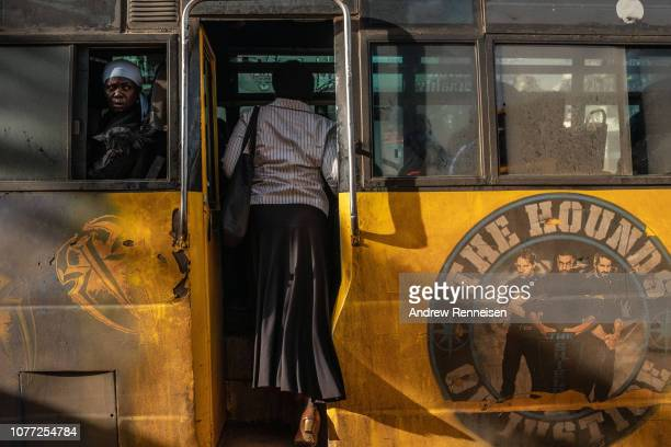 A woman boards a matatu at a bus stop on December 04 2018 in Nairobi Kenya The private minibuses were to have been banned from the city's central...