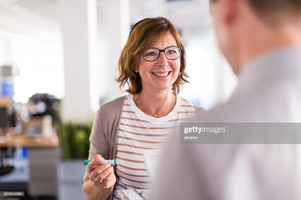 Woman boss speaking with her colleague : Stock Photo