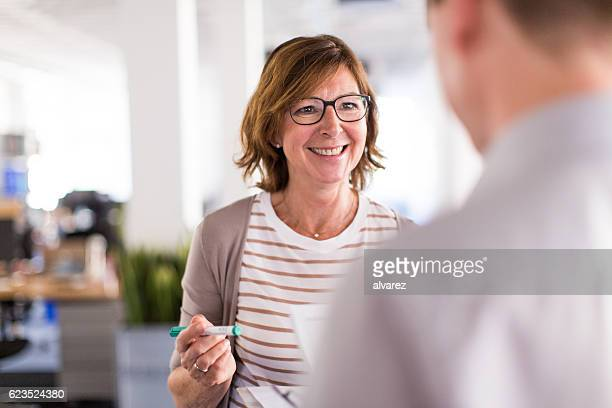 woman boss speaking with her colleague - witte boorden werker stockfoto's en -beelden