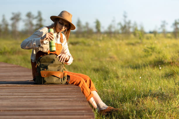 Woman Botanist In Hat Sitting On Wooden Path Through Peat Bog Swamp, Takes A Thermos From A Backpack