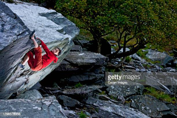 woman bouldering on rock at slate quarry in north wales - wales stock pictures, royalty-free photos & images