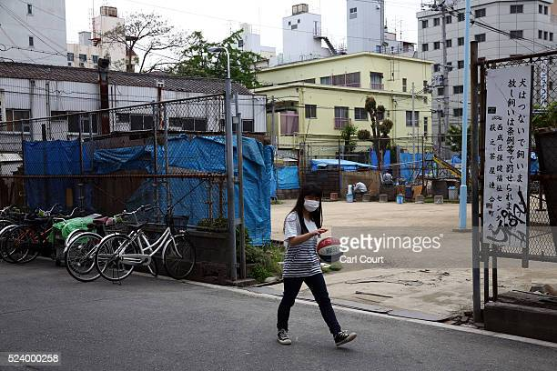 A woman bounces a basketball as she walks past an entrance to the slum area of Kamagasaki on April 24 2016 in Osaka Japan Kamagasaki a district in...
