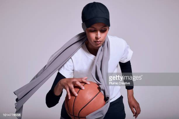 Woman bouncing basket ball