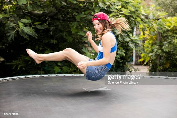 woman bouncing on trampoline - bouncing stock pictures, royalty-free photos & images