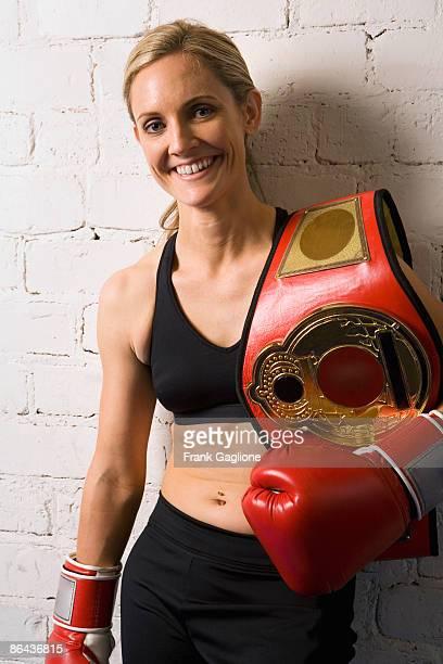 Woman Boxer Holding a Title Belt.