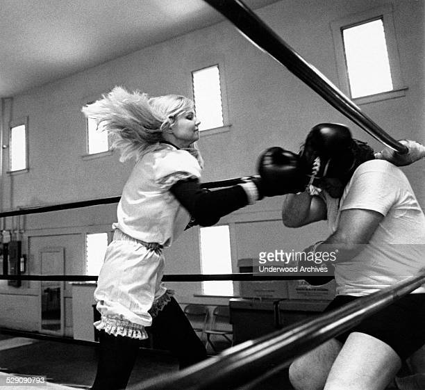 A woman boxer pummels her sparring partner that she has backed into a corner circa 1969