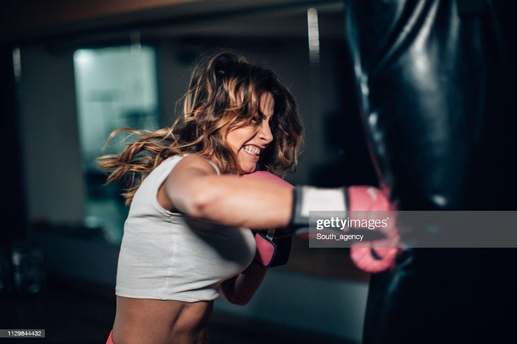 Woman boxer punching a punching bag : Stock Photo
