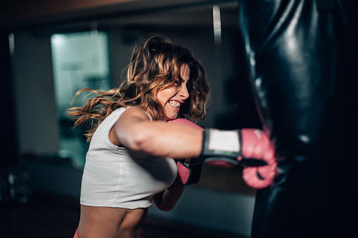 Woman boxer punching a punching bag 1129844432