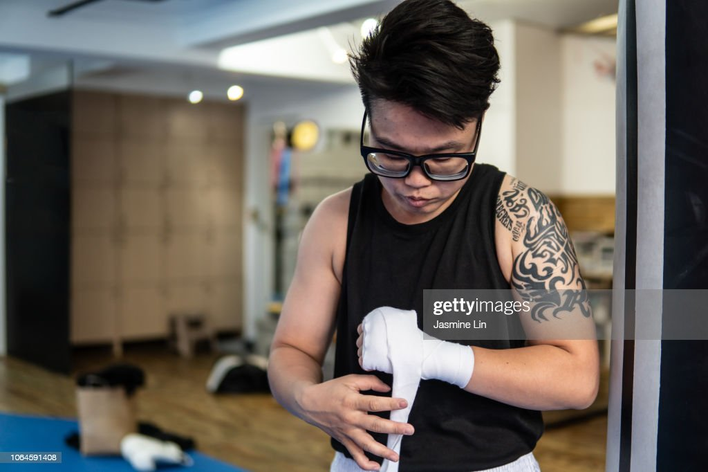 Woman boxer wrapping hands : Stock Photo