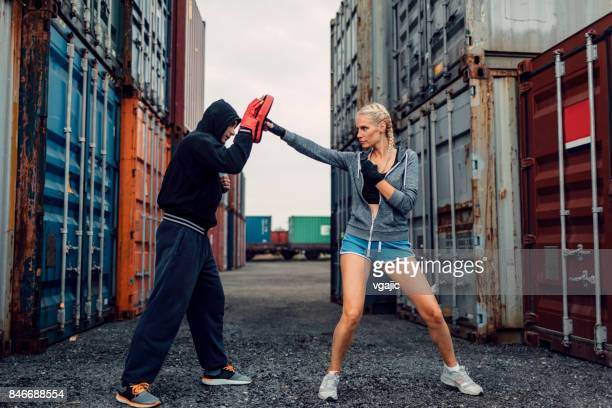 woman boxing with her personal trainer - women's boxing stock pictures, royalty-free photos & images
