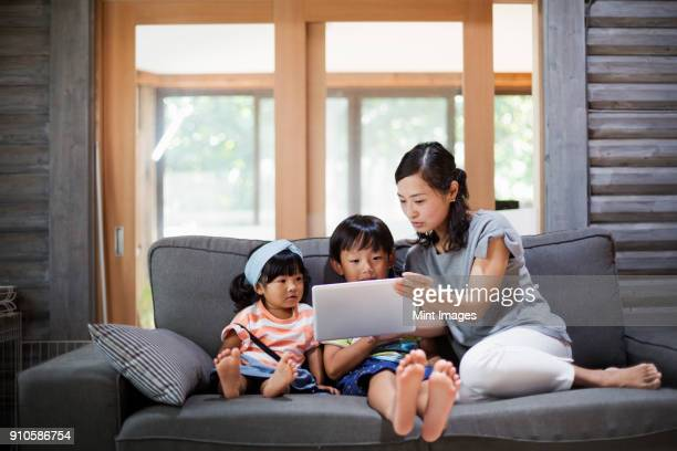 Woman, boy and young girl sitting on a grey sofa, looking at digital tablet.