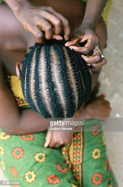 woman braiding girl's hair - コーンロウ ストックフォトと画像