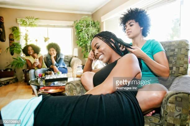 Woman braiding hair of friend in livingroom