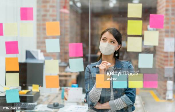 woman brainstorming at the office while wearing a facemask - business plan stock pictures, royalty-free photos & images