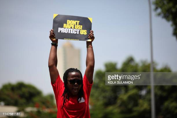 Woman brandishes a placard during a protest to challenge impunity and gender-based discrimination raids on women by Federal Capital Territory and...