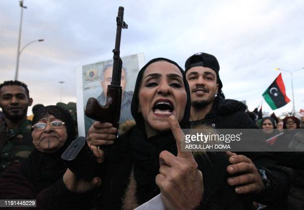 A woman brandishing a rifle takes part in a demonstration held by Libyans and Syrians in the eastern Libyan city of Benghazi to protest against...